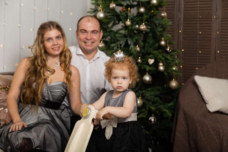 Beautiful young happy family with a child on New Years Eve on the couch. New Year 2020. Archivio Fotografico - 135866663