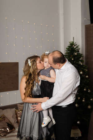 Beautiful young happy family with a child in her arms on New Years Eve. New Year 2020. Archivio Fotografico - 135866674
