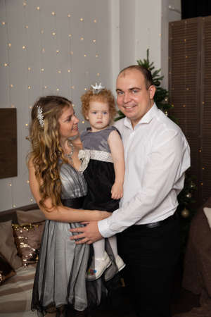 Beautiful young happy family with a child in her arms on New Years Eve. New Year 2020. Archivio Fotografico - 135866676