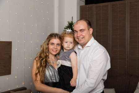 Beautiful young happy family with a child in her arms on New Years Eve. New Year 2020. Archivio Fotografico - 135866681