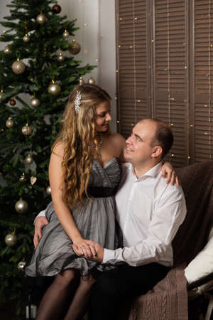 Beautiful and happy man and woman at the New Year tree on the couch. Happy New Year. Archivio Fotografico - 135866685