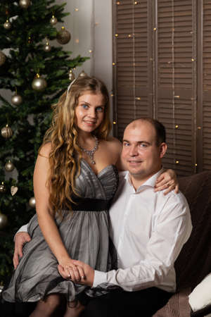Beautiful and happy man and woman at the New Year tree on the couch. Happy New Year. Archivio Fotografico - 135866686