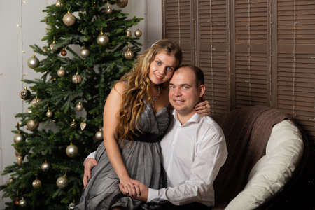Beautiful and happy man and woman at the New Year tree on the couch. Happy New Year. Archivio Fotografico - 135866687
