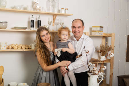 Happy family with a child in the kitchen in the New Year. Archivio Fotografico - 135866689