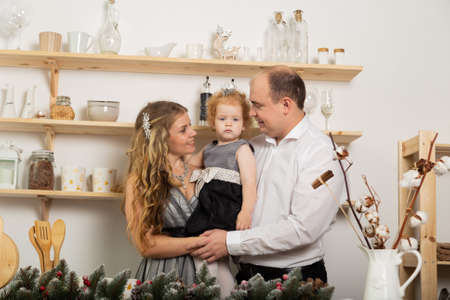 Happy family with a child in the kitchen in the New Year. Archivio Fotografico - 135866733