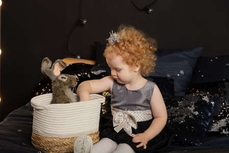 Beautiful little girl child on a New Years bed with an artificial rabbit. Archivio Fotografico - 135866744