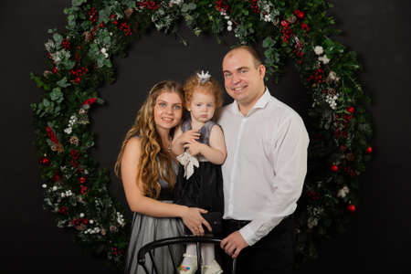 Beautiful young happy family with a child in her arms on New Years Eve. New Year 2020. Archivio Fotografico - 135866819
