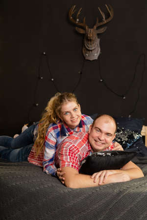 Beautiful couple in love on a Christmas bed. New Year 2020. Archivio Fotografico - 135866869