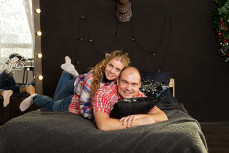 Beautiful couple in love on a Christmas bed. New Year 2020. Archivio Fotografico - 135866874