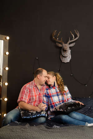 Beautiful couple in love on a Christmas bed. New Year 2020. Archivio Fotografico - 135866878
