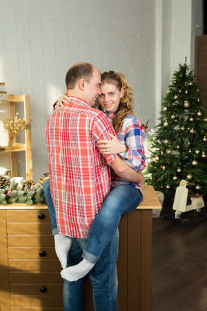 Beautiful happy couple in love cuddles in the Christmas kitchen in the new year 2020