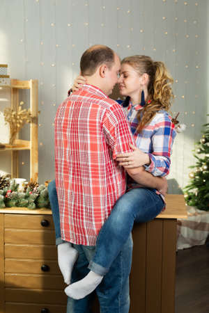 Beautiful happy couple in love cuddles in the Christmas kitchen in the new year 2020 Archivio Fotografico - 135866984