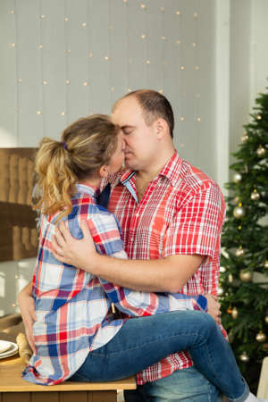 Beautiful happy couple in love cuddles in the Christmas kitchen in the new year 2020 Archivio Fotografico - 135866997