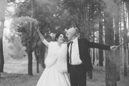 Gelukkige bruid en bruidegom houden gekleurde rook in hun handen. Stockfoto