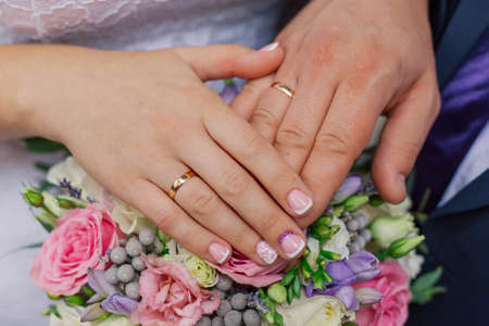 Beautiful hands with wedding rings of the newlyweds on a bouquet. Standard-Bild - 140193245