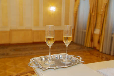 Beautiful crystal glasses with champagne on a tray.