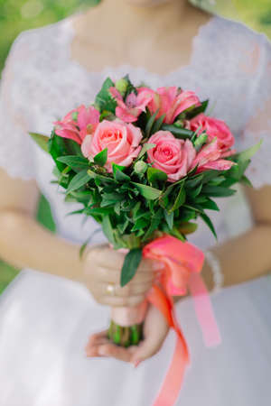 Young happy bride with a wedding bouquet by a bouquet.