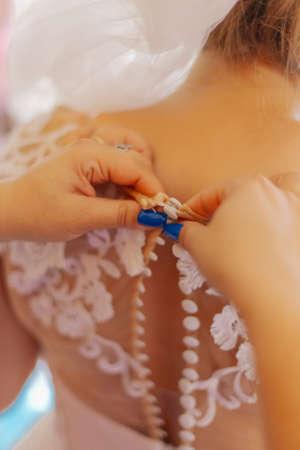A young bride buttoned wedding dress. Happy wedding day. 版權商用圖片