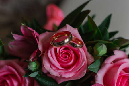 New wedding rings next to the brides bouquet.