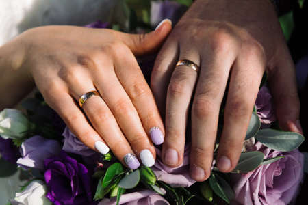 Beautiful hands with wedding rings of the newlyweds on a bouquet. Standard-Bild - 140204187