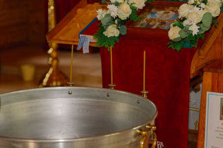 Silver baptismal font with burning candles in a church.