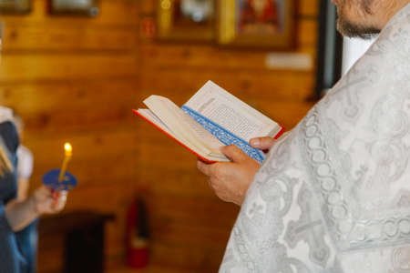 Old priest hands on the bible in the church at the altar.