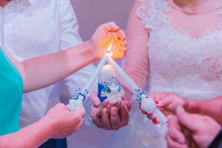 Beautiful newlyweds light a candle at a wedding celebration.