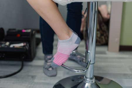 Beautiful legs of a woman in socks on a chair. 版權商用圖片