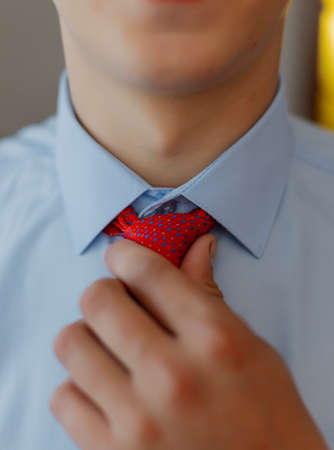 A young man puts on a tie. Businessman.