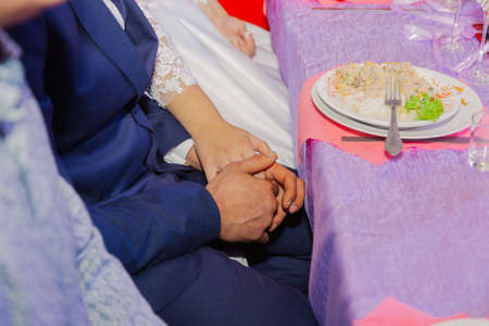 Beautiful newlyweds holding hands sitting at the festive table.