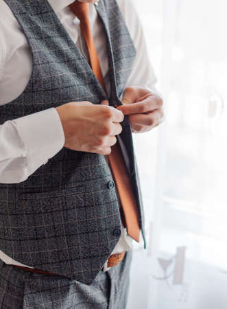 A man and a successful businessman straightens his jacket.