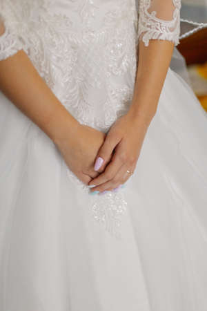 Young bride hands on a wedding dress