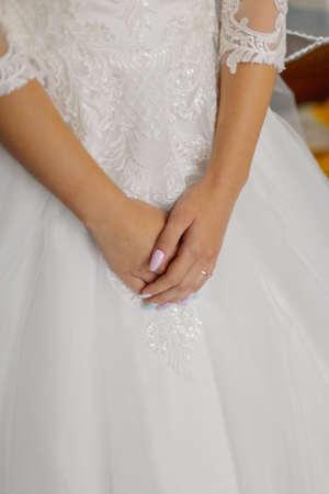 Jeune mariée mains sur une robe de mariée