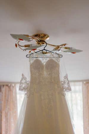 Beautiful wedding dress on a hanger on a happy wedding day. 版權商用圖片