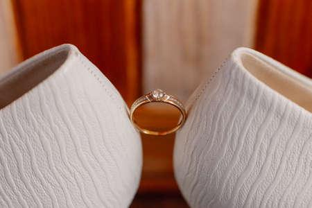 Wedding womens shoes with a wedding ring illuminated by photo light. 版權商用圖片