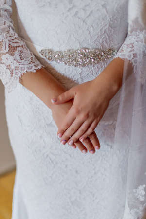 Young bride hands on a wedding dress.