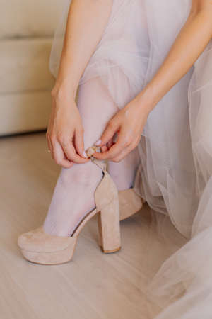 Young bride closes shoes on a happy wedding day.