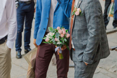 Beautiful young stylish groom with a wedding bouquet in his hand. 版權商用圖片