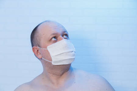 Portrait of a bald man who is in a medical mask.