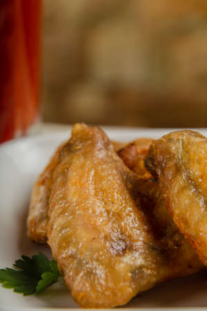 Fresh fried chicken wings on a white plate.