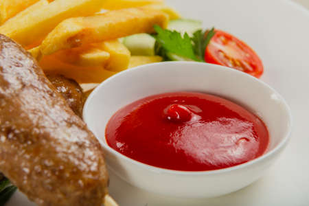 Freshly fried kebab with fried potatoes and tomato sauce on a white plate. Stockfoto