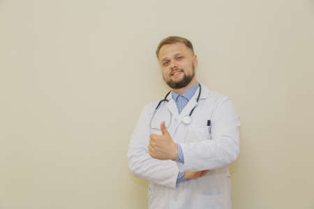 Male doctor holds a thumb up. Happy doctor.