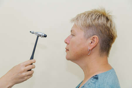 Woman neurologist examines a patient with a hammer in a private clinic Archivio Fotografico