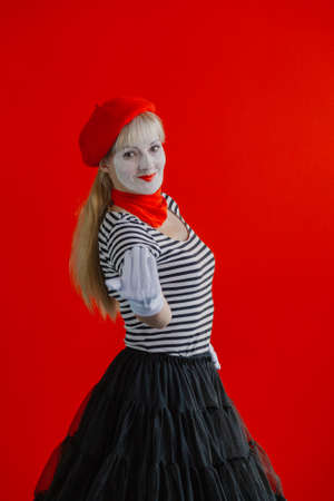Woman mime near a red wall in a red beret shows a sign with her hand.