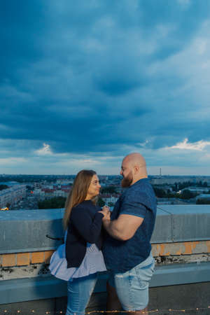 Beautiful and happy lovers on the roof hugging. Archivio Fotografico