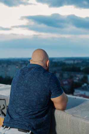 Big bearded bodybuilder on the rooftop in the evening. Archivio Fotografico