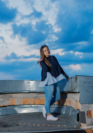 Beautiful young woman on the rooftop in the evening.