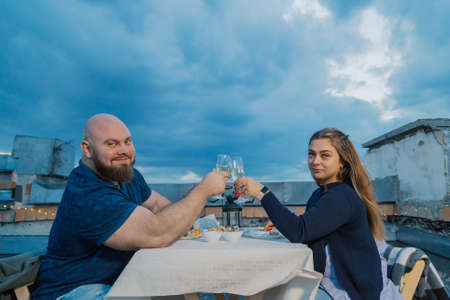 Lovers on the roof sit at a table.