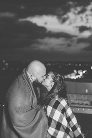 Beautiful couple on the roof under a blanket in the evening. Archivio Fotografico