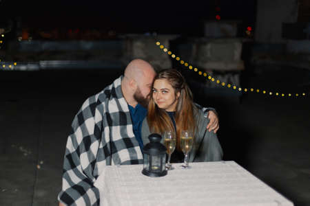 Lovers on the roof sit at a table with champagne.